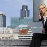 A beautiful young female executive talking on her cell phone and working on her laptop in a hi-tech urban surrounding